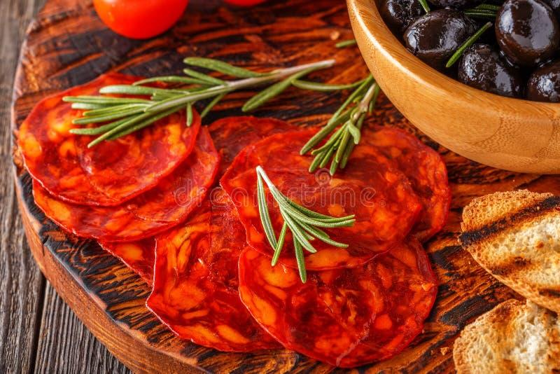 Salchicha tradicional española del chorizo con las hierbas frescas, aceitunas imagen de archivo