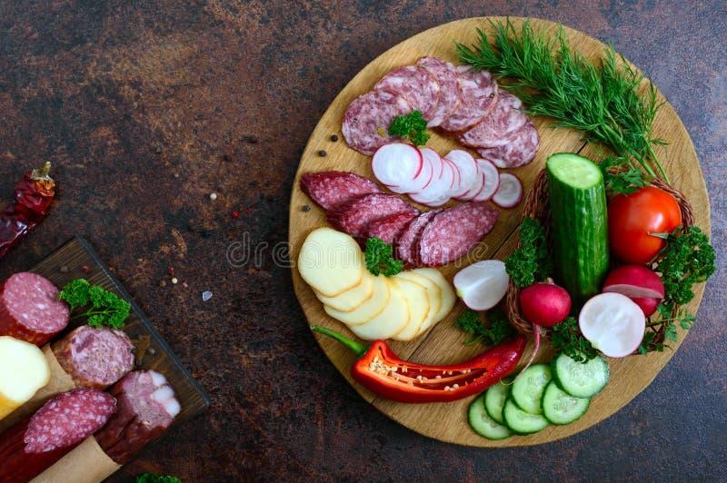 Salchicha y verduras frescas cortadas en una bandeja de madera Bandeja del bocado imagenes de archivo