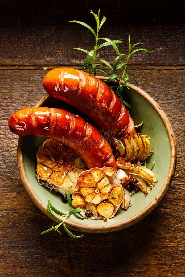 Salchichas asadas a la parrilla con ajo, la cebolla y el romero de la adición en una tabla de madera rústica imagen de archivo libre de regalías