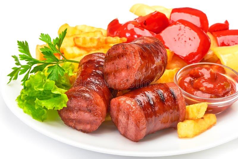Salchichas asadas a la parrilla con las fritadas de las patatas y la salsa de tomate búlgara dulce del pimienta y roja de la sals imágenes de archivo libres de regalías