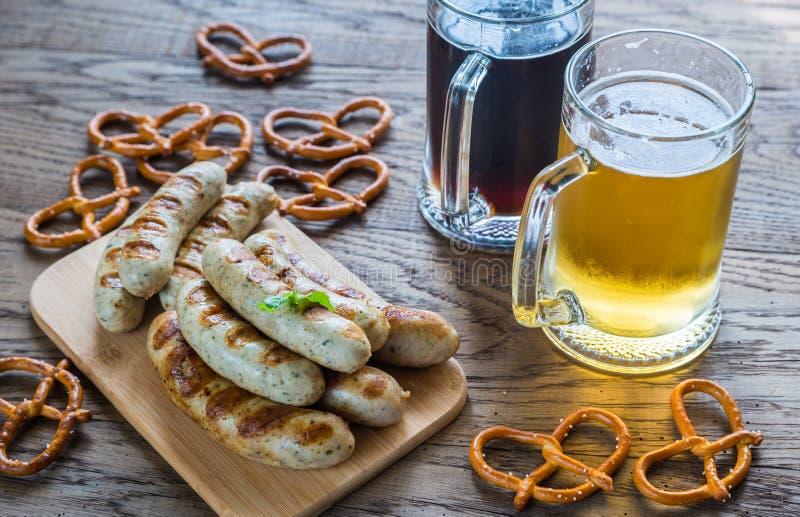 Salchichas asadas a la parrilla con los pretzeles y las tazas de cerveza foto de archivo