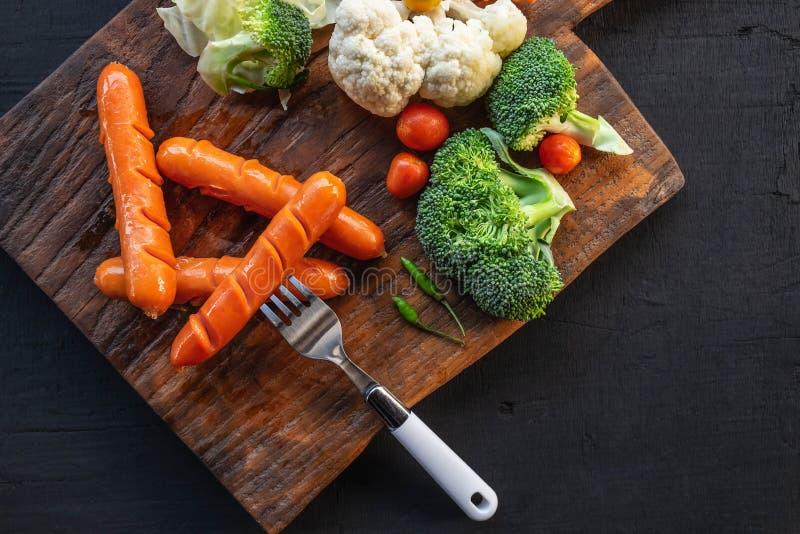 Salchichas asadas a la parrilla deliciosas y verduras sanas en una tabla de madera imágenes de archivo libres de regalías