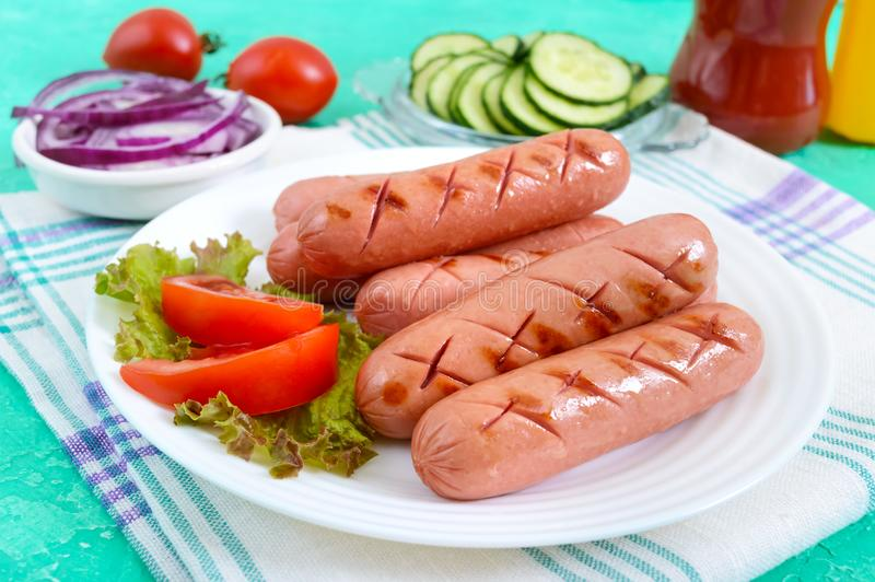 Salchichas asadas a la parrilla jugosas deliciosas en una placa, verduras, salsa de tomate y mostaza fotografía de archivo