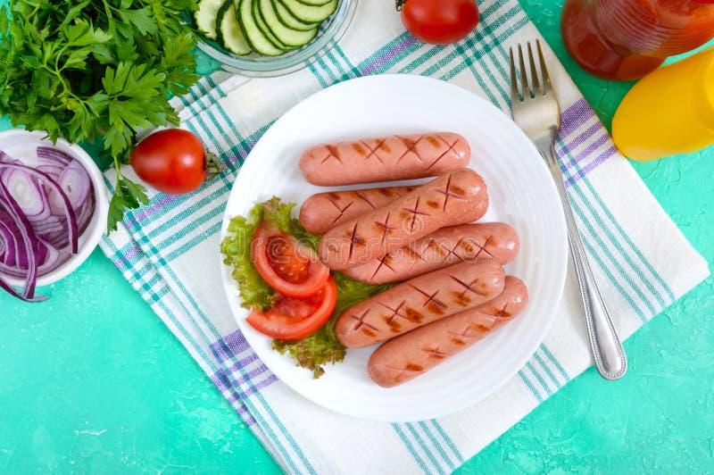 Salchichas asadas a la parrilla jugosas deliciosas en una placa, verduras, salsa de tomate y mostaza foto de archivo