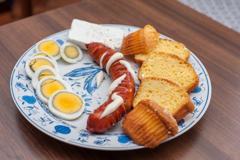 Salchichas asadas a la parrilla sabrosas con queso y huevos en la placa en la tabla de madera fotografía de archivo libre de regalías