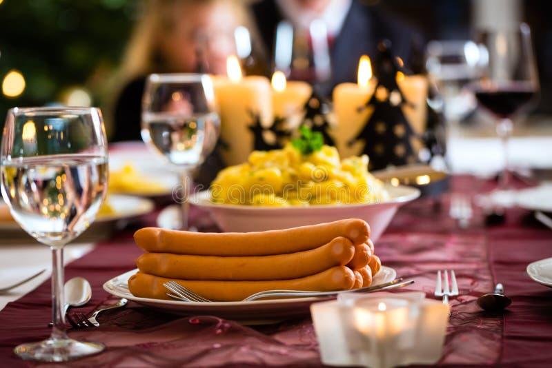 Salchichas de la cena de la Navidad de la familia y ensalada de patata imagen de archivo