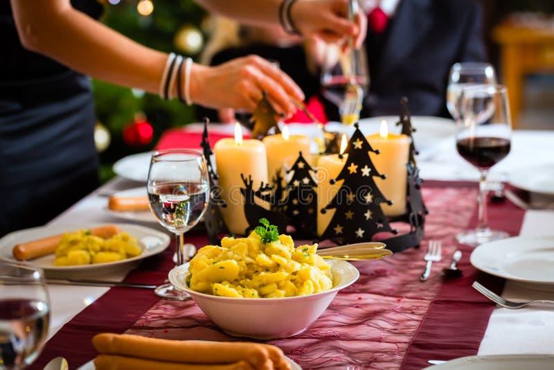 Salchichas de la cena de la Navidad de la familia y ensalada de patata fotografía de archivo libre de regalías