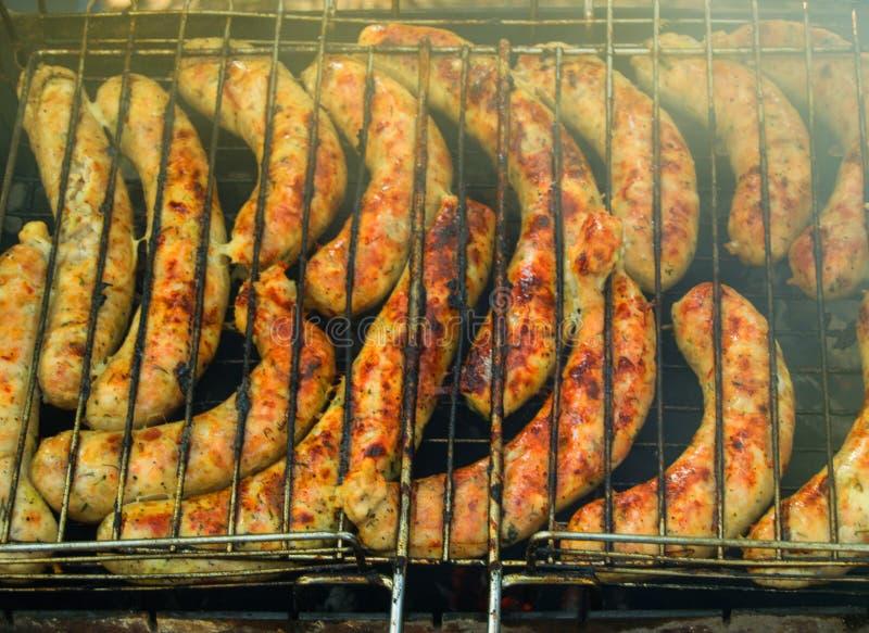 Salchichas deliciosas asadas a la parrilla sobre el fuego en un aire libre de la comida campestre, primer, FONDO de la COMIDA foto de archivo