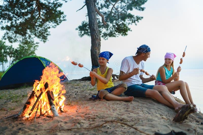 Salchichas felices de la asación de la familia sobre hoguera concepto el acampar y del turismo fotografía de archivo libre de regalías