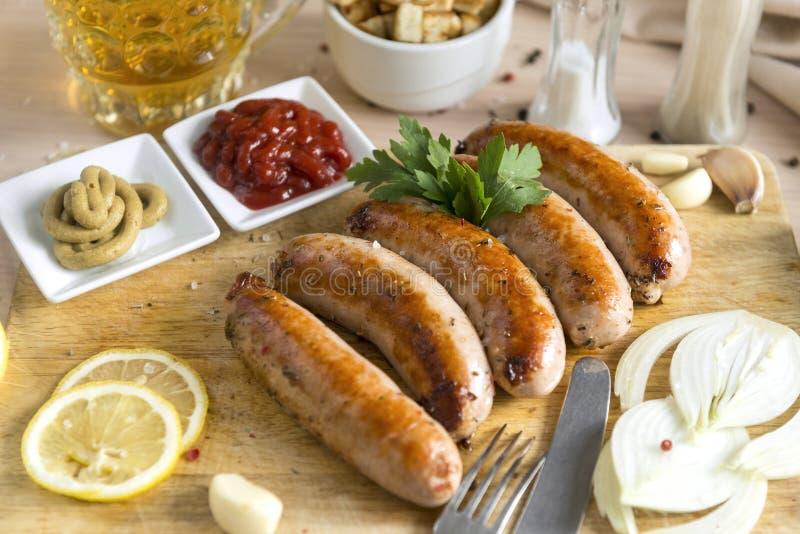 Salchichas fritas de la carne en la tabla de cortar, salsa de tomate, mostaza, cebolla, verdes, limón, ajo, taza de cerveza liger imagen de archivo
