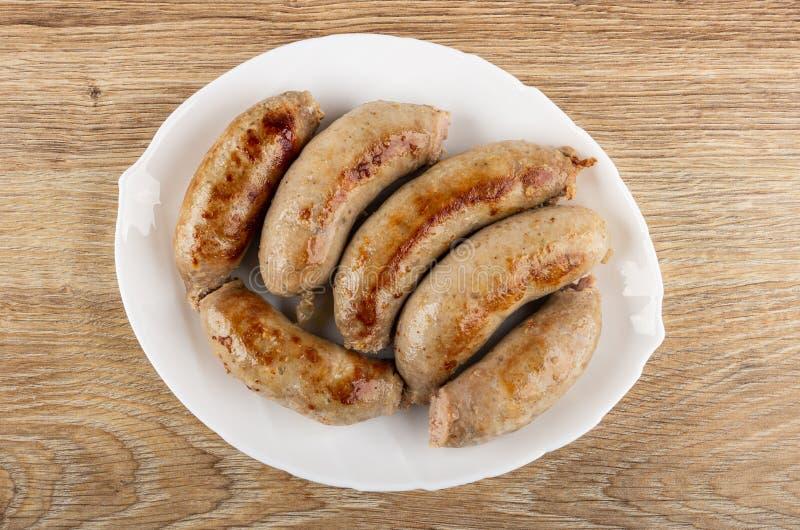 Salchichas fritas en cáscara natural en el plato blanco en la tabla Visi?n superior fotografía de archivo