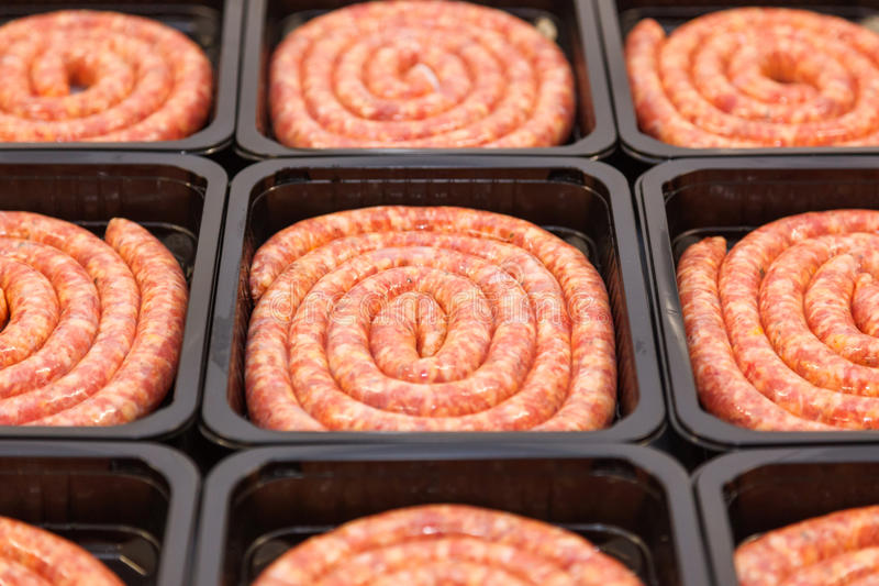 Salchichas rodadas de la carne cruda en caja de embalaje fotografía de archivo