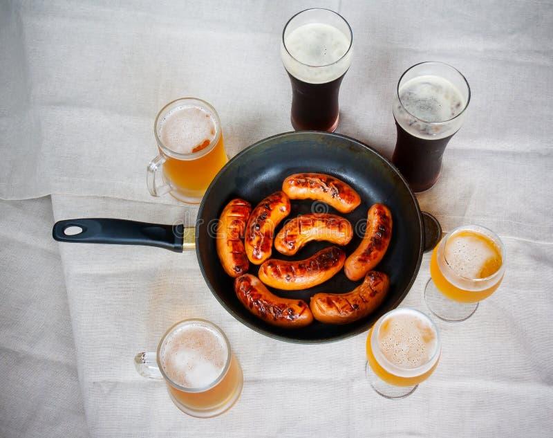 Salchichas y vidrios de cerveza asados a la parrilla en la tabla Visión superior imagen de archivo libre de regalías
