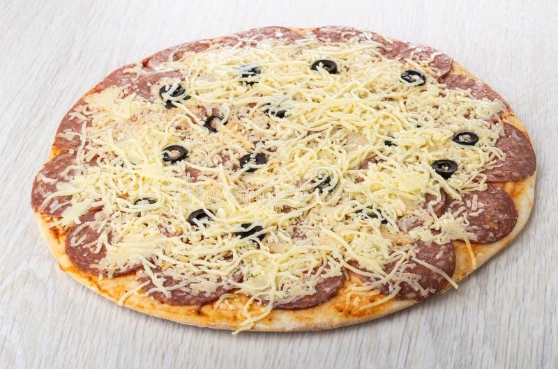 Salchichones crudos de la pizza en la tabla de madera imágenes de archivo libres de regalías