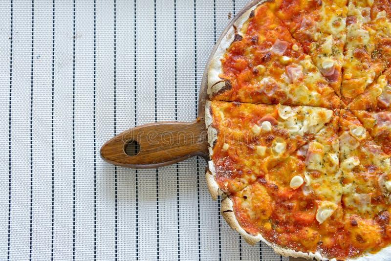 Salchichones y jamón de la pizza de Homermade en la bandeja de madera con los vagos blancos de la estera imagenes de archivo