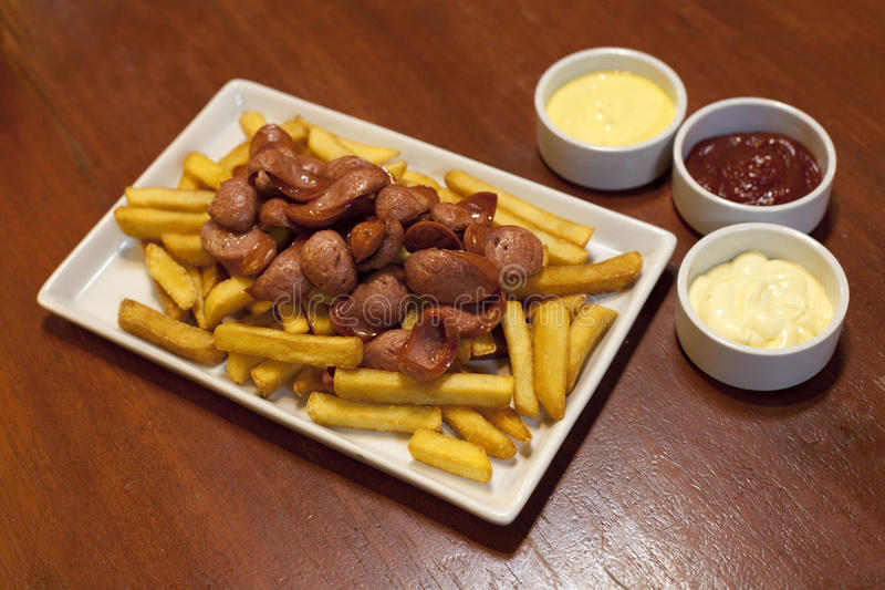 Salchipapas, typical Peruvian food. Fried potatoes and sausages royalty free stock image