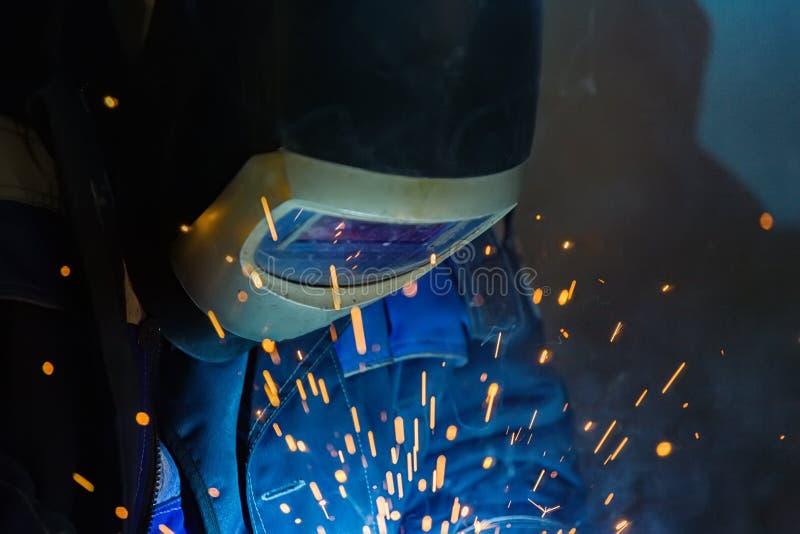 Saldatore negli impianti del casco nel negozio Scintille luminose dalla saldatura del metallo immagini stock
