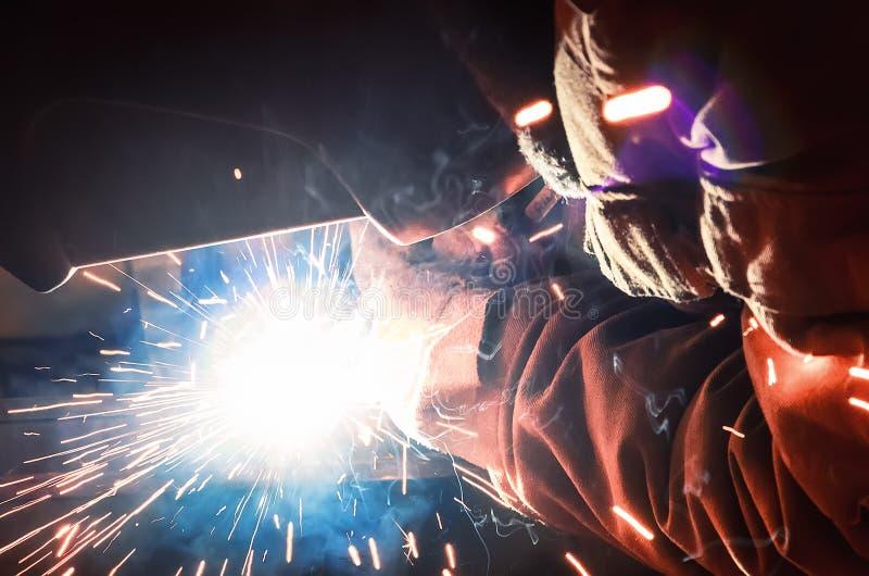 Saldatore in una maschera protettiva nelle parti di buio della fabbrica di metallo della saldatura Saldando le scintille volano n fotografie stock