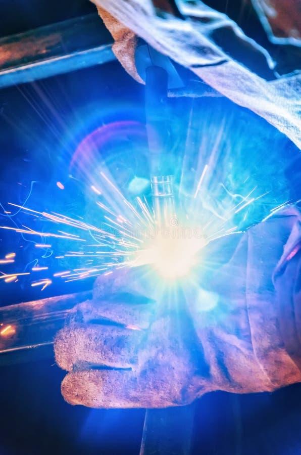 Saldatore in una maschera protettiva nelle parti di buio della fabbrica di metallo della saldatura Saldando le scintille volano n immagine stock libera da diritti