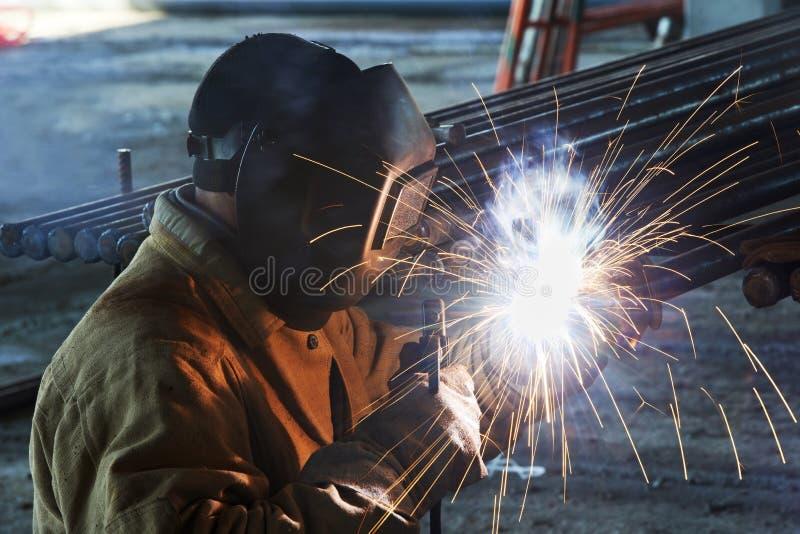 Saldatura del lavoratore con l'elettrodo dell'arco elettrico fotografie stock
