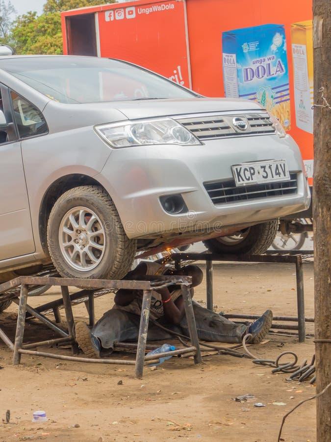Saldatura keniana del meccanico sotto l'automobile in via immagini stock