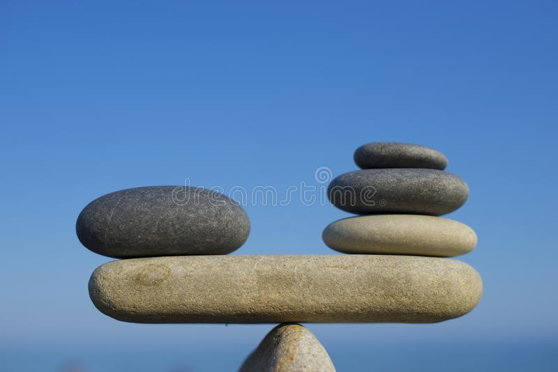 Saldo van stenen Aan gewichtspros - en - cons. In evenwicht brengende stenen op de bovenkant van kei Sluit omhoog stock fotografie