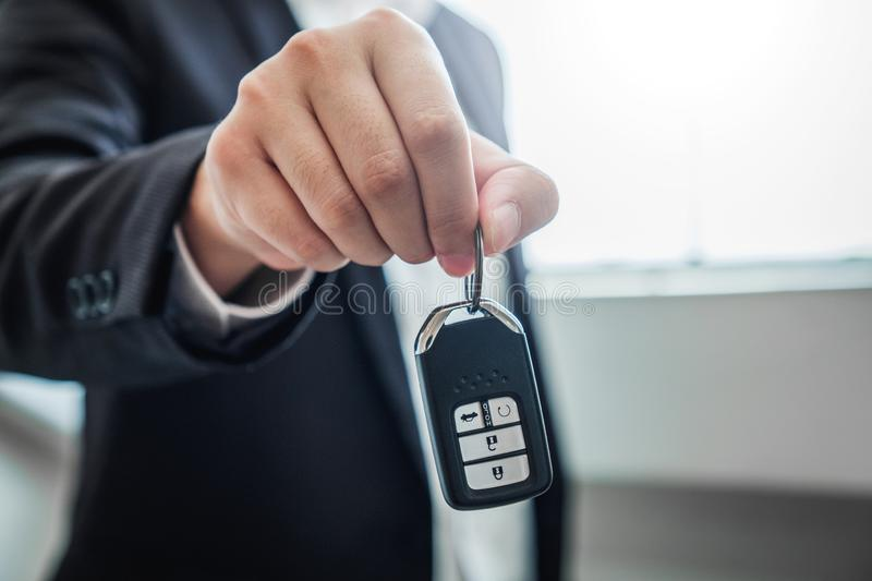 Sale agent giving Car key to customer and sign agreement contract, Insurance car concept stock photography