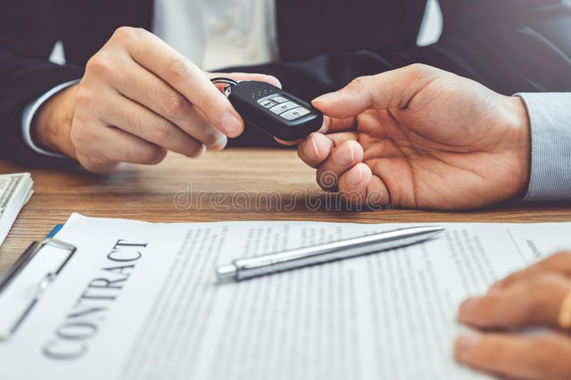 Sale agent giving Car key to customer and sign agreement contract, Insurance car concept stock images