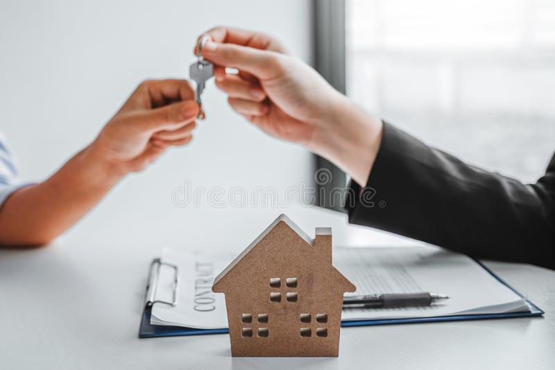 Sale Agent giving house keys to woman customer and sign agreement documents for realty purchase stock photos