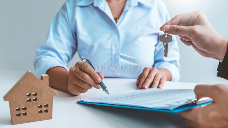 Sale Agent giving house keys to woman customer and sign agreement documents for realty purchase stock image