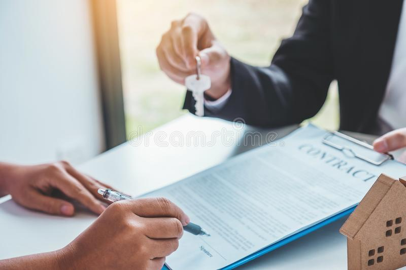 Sale Agent giving house keys to woman customer and sign agreement documents for realty purchase stock photography