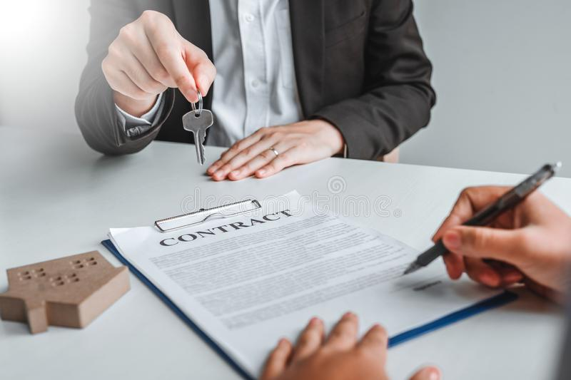 Sale Agent giving house keys to woman customer and sign agreement documents for realty purchase royalty free stock image
