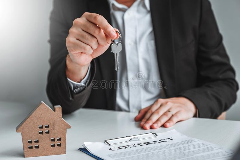 Sale Agent giving house keys to woman customer and sign agreement documents for realty purchase royalty free stock photography