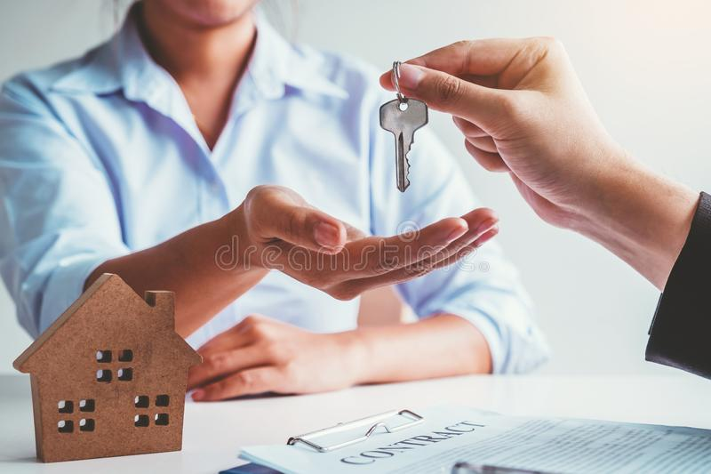 Sale Agent giving house keys to woman customer and sign agreement documents for realty purchase stock photo