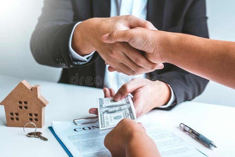 Sale Agent handshake with woman customer and sign agreement documents for realty purchase after successful loan contract royalty free stock image
