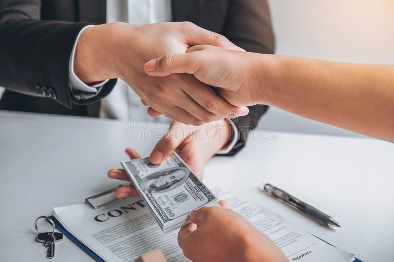 Sale Agent handshake with woman customer and sign agreement documents for realty purchase after successful loan contract stock photo