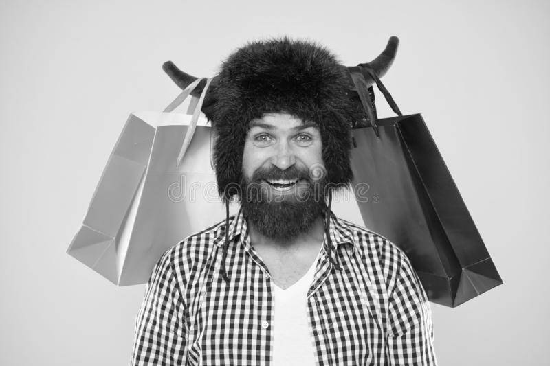 Sale, big savings no waiting. Bearded man smiling with purchases bought at sale. Happy hipster in bull horns hat holding royalty free stock image