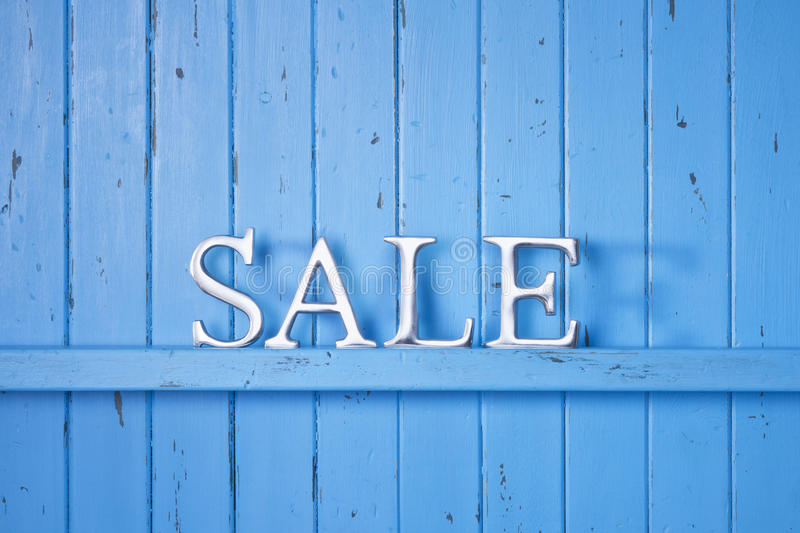 Sale Wood Blue Background Banner. A blue painted rustic wood background with a shelf or crossbeam with the word SALE