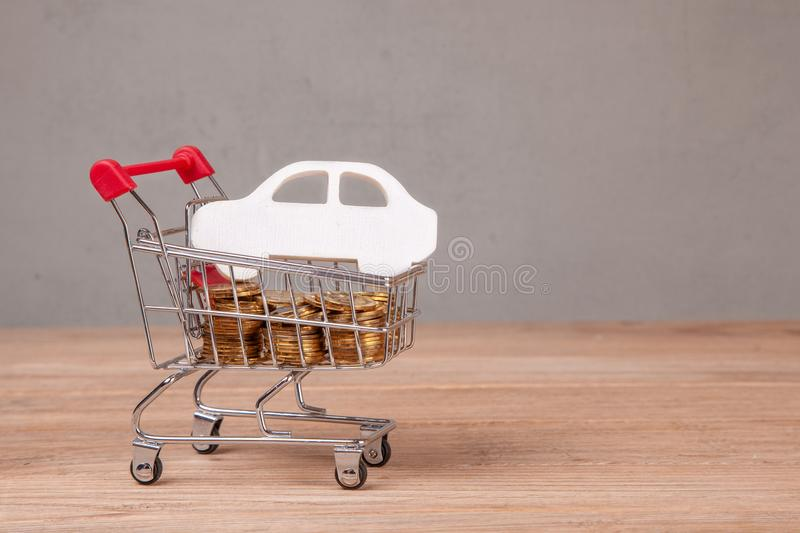 Sale or buy car. Shopping cart full of coins and car symbol.  royalty free stock images