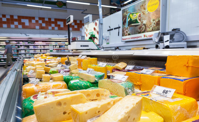 Sale of cheese in the hypermarket Karusel. One of largest retai. VYBORG, RUSSIA - AUGUST 6, 2015: Sale of cheese in the hypermarket Karusel. One of largest royalty free stock photos