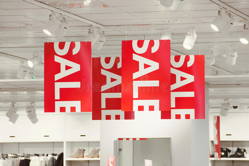 Sale signs in a clothing store. Sale signs hanging from the ceiling stock photography