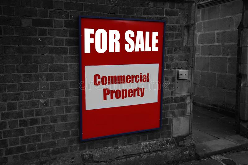 For sale with commercial property written on a sign attached to a wall. For sale with commercial property written on a sign attached to a brick wall with stock photos