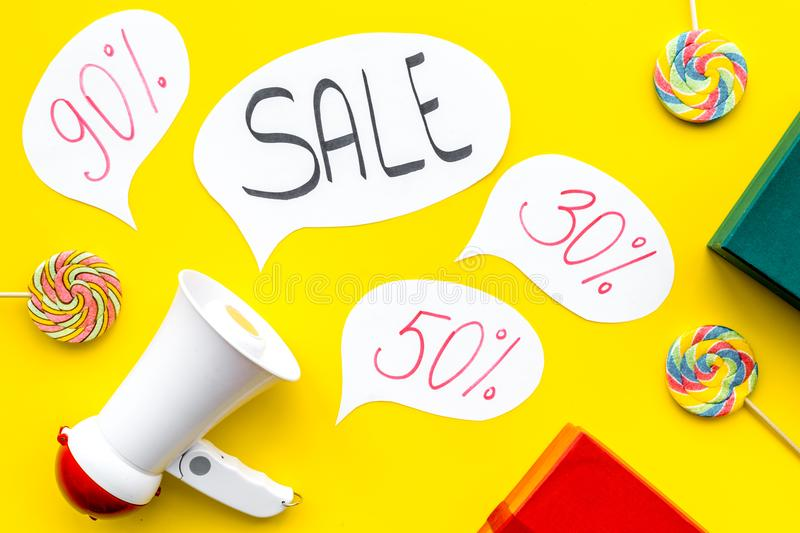 Sale concept with megaphone. Declare the sale. Electronic megaphone near word sale in cloud, gift boxes and sweets on stock image