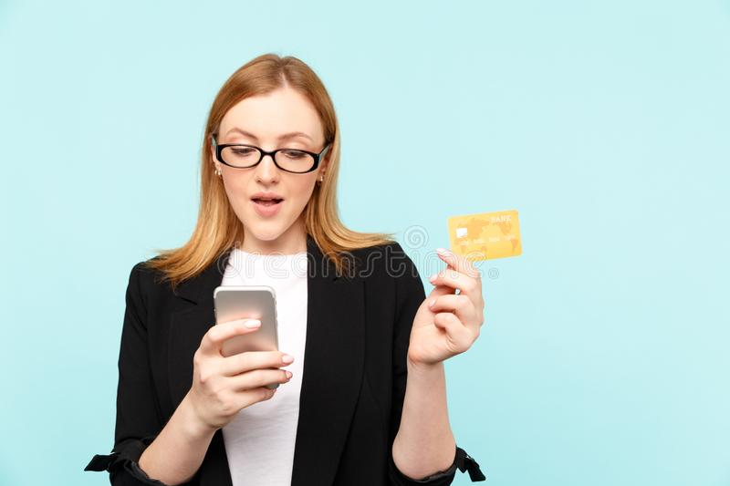 Sale concept. Woman holding credit card with phone and using it to make shopping online. Sale concept. Woman holding credit card with phone and using it to make stock photo