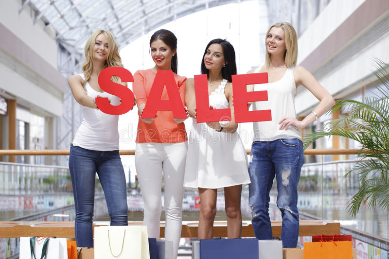 Sale concept. Women with red sale letters in mall, shopping concept royalty free stock photography