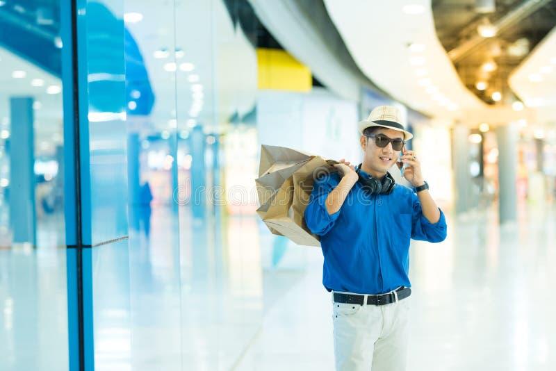 Sale, consumerism och folkbegrepp - lycklig ung asiatisk manintelligens arkivfoto