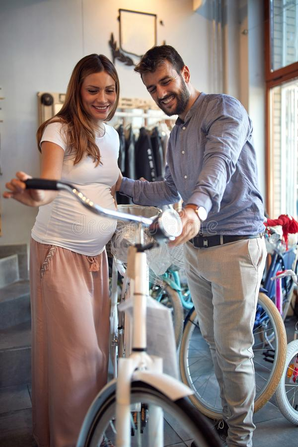 Sale, consumerism and people concept - couple choosing new bicycle royalty free stock photography
