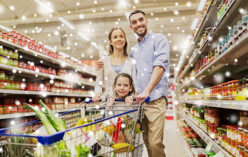 Family with food in shopping cart at grocery store stock image