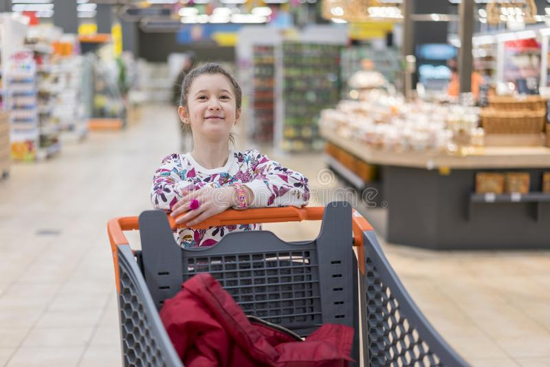 sale, consumerism and people concept - happy little girl with food in shopping cart at grocery store stock image
