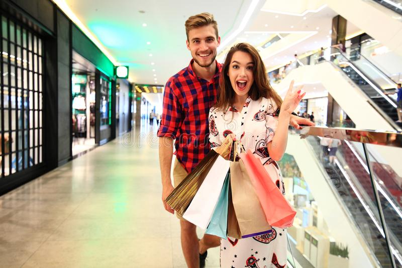 Sale, consumerism and people concept - happy young couple with shopping bags walking in mall. royalty free stock photo